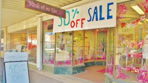 "The Blink of an Eye storefront displays a ""50% off sale"" banner. The sale will continue until the store closes March 31. There will be a closing celebration at the store that same day."