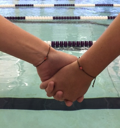 Members of the Truman State swim team pose with their Orange Bead Collective wristbands, supporting those who have mental illnesses. Photo submitted by Emily Ponte