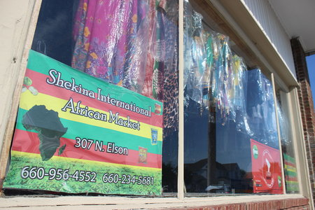 Shekina International African Market is open for business with traditional African outfits and colorful posters in the window displays.