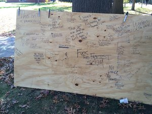 People at the protest wrote their feelings about the election on a giant piece of wood on the quad.