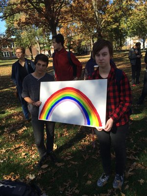 Truman students hold up a rainbow, a symbol for gay pride, at the Dump Trump rally.