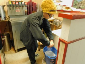 Junior Kay Harvey in a yellow beanie wringing materials out over a bucket of liquid while working at China Palace.