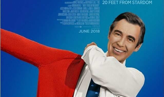 A redrawing of Fred Rogers smiling and putting on a red sweater.