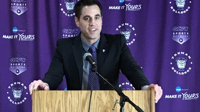 Jeff Horner behind a podium with a purple curtain behind him, for a press conference